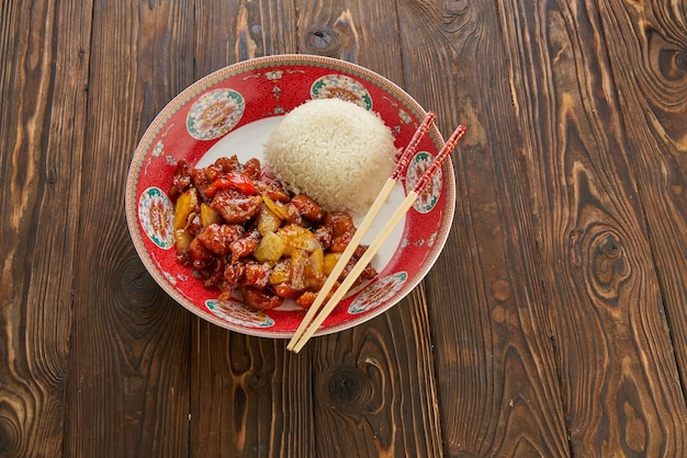 中華料理、ピーマン、タマネギ、パイナップルを添えた甘酸っぱい揚げ豚肉のチャンク、箸を使った伝統的な赤いプレート、白いボウルにご飯を入れた古い木製のテーブル