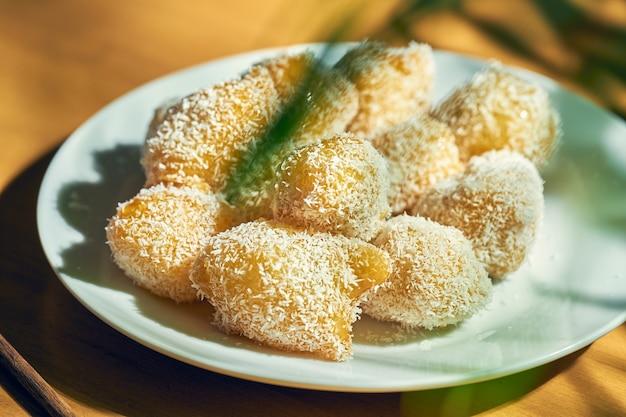 Китайский десерт - жареные в карамели яблоки с кокосовой стружкой в белой тарелке. китайская кухня