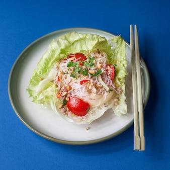 새해 중국 요리. 접시, 평면도, 복사 공간에 야채 샐러드와 쌀 국수.
