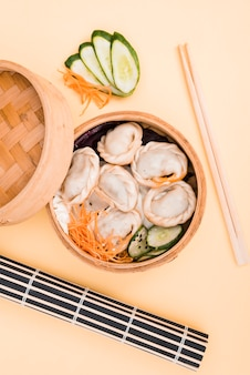 Chinese dumpling and salad in a bamboo steamer box on colored backdrop with chopsticks