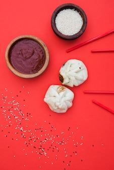 Китайские пельмени с соусами на ужин с миской кунжута и палочками на красном фоне