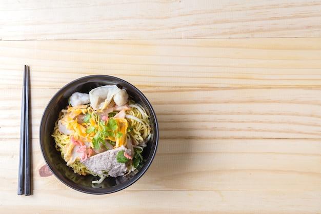 중국 계란 국수와 나무 테이블에 돼지 고기