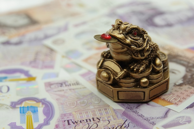 Chinese feng shui lucky money frog sitting on 20 uk pounds banknotes. closeup