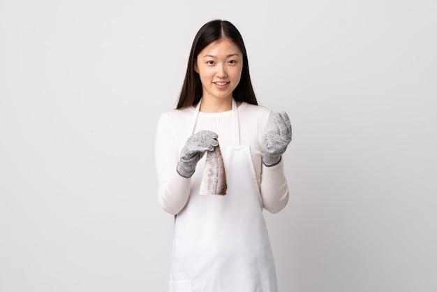 앞치마를 입고 고립 된 흰색에 생선을 들고 돈 제스처를 만드는 중국 생선 장수