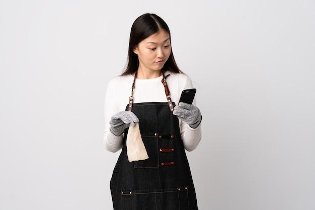 앞치마를 입고 고립 된 흰색 배경 위에 생선을 들고 생각하고 메시지를 보내는 중국 생선 장수