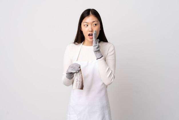 Китайский торговец рыбой в фартуке, держащий сырую рыбу на изолированном белом фоне, шепчет что-то с удивленным жестом, глядя в сторону