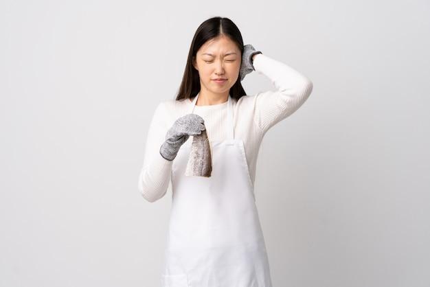 Китайский торговец рыбой, носящий фартук и держащий сырую рыбу над изолированными белыми расстроенными и покрывающими уши