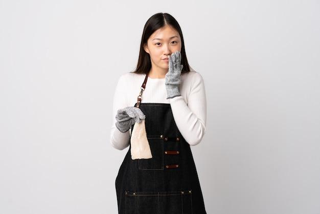 중국 생선 장수는 앞치마를 입고 격리 된 흰색 위에 생선을 들고 행복하고 손으로 입을 덮고 웃고 있습니다.