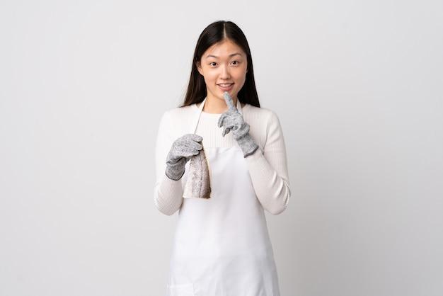 앞치마를 입고 입에 손가락을 넣어 침묵 제스처의 표시를 보여주는 격리 된 흰색 위에 생선을 들고 중국 생선 장수