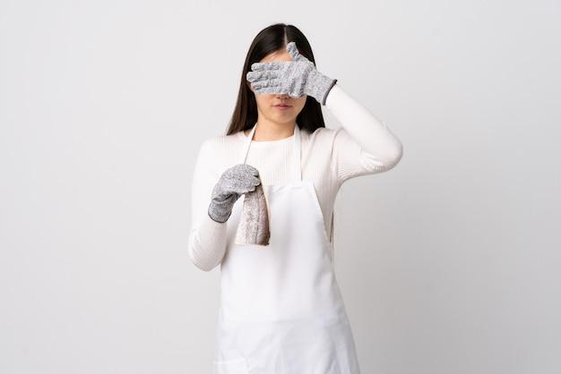 Китайский торговец рыбой в фартуке держит сырую рыбу над изолированной белой стеной, закрывая глаза руками. не хочу что-то видеть