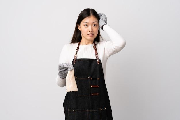 中国の魚屋、エプロンを着用し、神経質なジェスチャーを行う孤立した白い壁に生の魚を保持