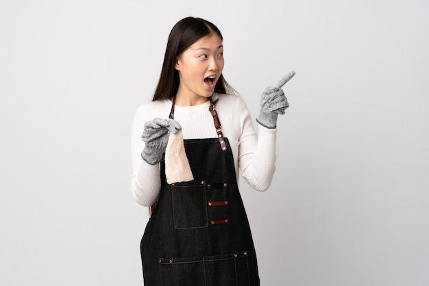 Китайский торговец рыбой в фартуке и держит сырую рыбу над изолированной белой стеной, намереваясь найти решение, подняв палец вверх