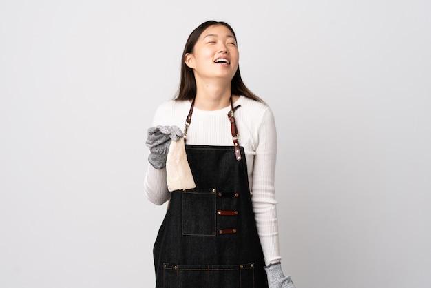 Китайский торговец рыбой в фартуке, держащий сырую рыбу над изолированной белой стеной, смеется