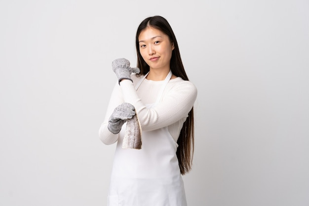 Китайский торговец рыбой в фартуке, держащий сырую рыбу над изолированной белой стеной, гордый и самодовольный