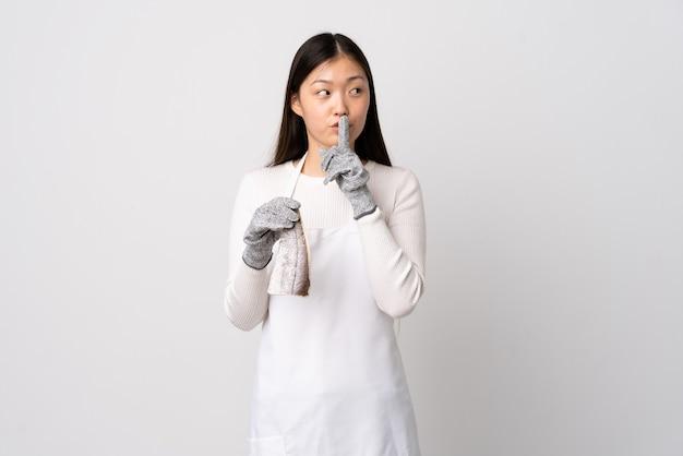 Китайский торговец рыбой в фартуке и держит сырую рыбу над изолированной белой стеной, показывая жест молчания, кладя палец в рот