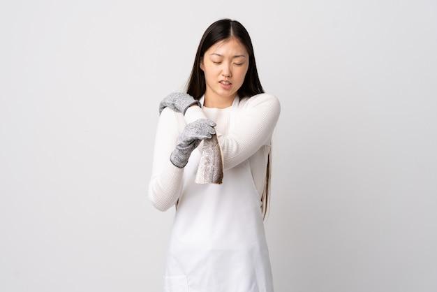 Китайский торговец рыбой, носящий фартук и держащий сырую рыбу над изолированной белой стеной, страдающий от боли в плече из-за усилий