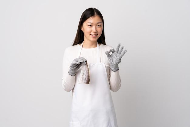 中国の魚屋、エプロンを着て、白い壁に生の魚を両手でokの標識を表示