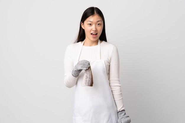 앞치마를 입고 깜짝 표정으로 흰색 위에 생선을 들고 중국 생선 장수