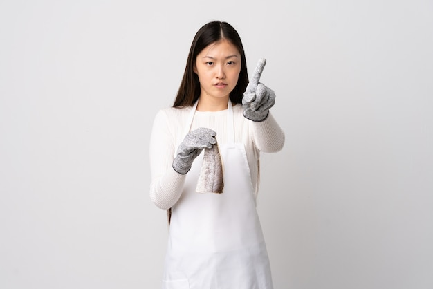 Chinese fishmonger wearing an apron and holding a raw fish over isolated white background counting one with serious expression