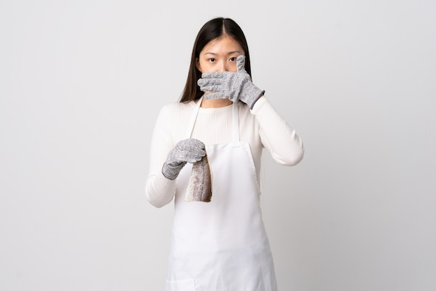 Chinese fishmonger wearing an apron and holding a raw fish over isolated white background covering mouth with hand