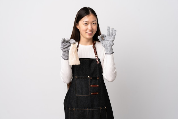 Chinese fishmonger wearing an apron and holding a raw fish over isolated white background showing ok sign with fingers