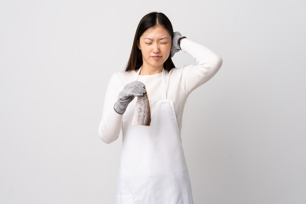 Chinese fishmonger wearing an apron and holding a raw fish over isolated white frustrated and covering ears