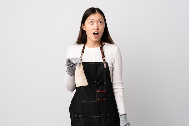 Chinese fishmonger wearing an apron and holding a raw fish over isolated white looking up and with surprised expression