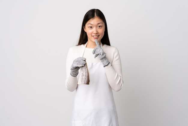 Chinese fishmonger wearing an apron and holding a raw fish over isolated white showing a sign of silence gesture putting finger in mouth