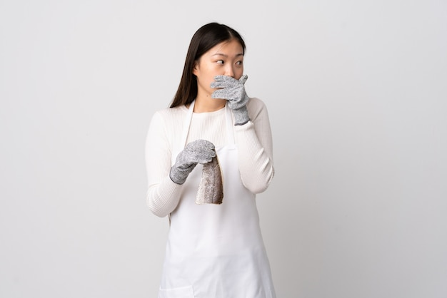 Chinese fishmonger wearing an apron and holding a raw fish over isolated white wall covering mouth and looking to the side