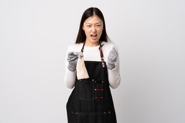 Chinese fishmonger wearing an apron and holding a raw fish over isolated white wall frustrated by a bad situation