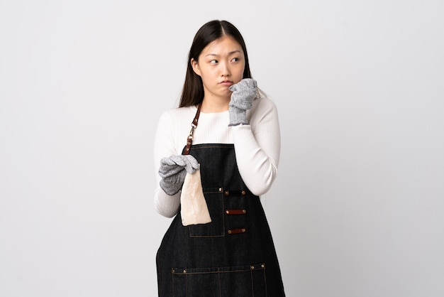 Chinese fishmonger wearing an apron and holding a raw fish over isolated white wall nervous and scared putting hands to mouth