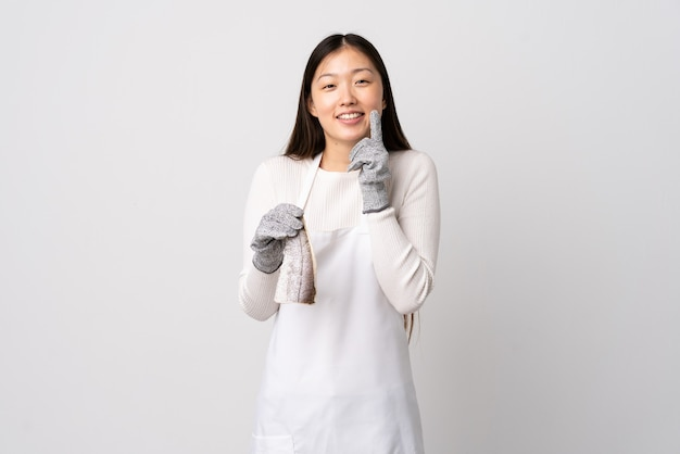 Chinese fishmonger wearing an apron and holding a raw fish over isolated white wall smiling with a happy and pleasant expression