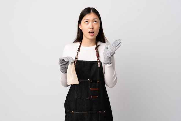 Chinese fishmonger wearing an apron and holding a raw fish over isolated white wall stressed overwhelmed