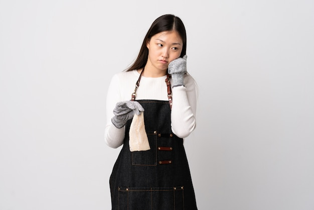 Chinese fishmonger wearing an apron and holding a raw fish over isolated white wall with tired and bored expression