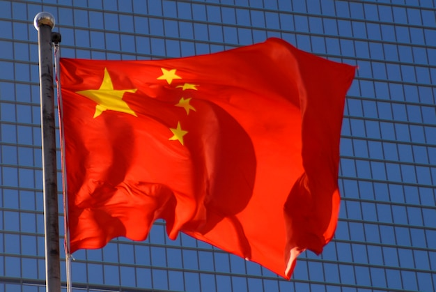 Chinese flag with a modern office building backdrop.