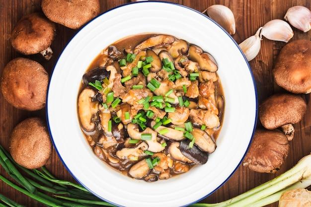 Китайская еда и грибы шиитаке, обжаренные с курицей