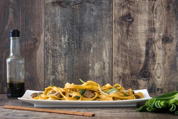 中華料理牛肉チャウメン木製テーブルの上の白いプレート