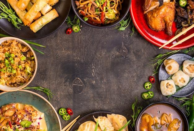 中華料理の暗い背景。中華麺、米、餃子、北京ダック、点心、春巻き