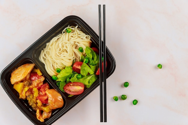 젓가락으로 플라스틱 용기에 중국 음식. 음식 배달 개념.