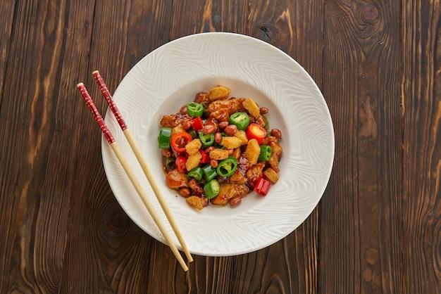 Китайская еда, курица кунг пао в белой тарелке с палочками для еды на деревянном столе, вид сверху и место для копирования