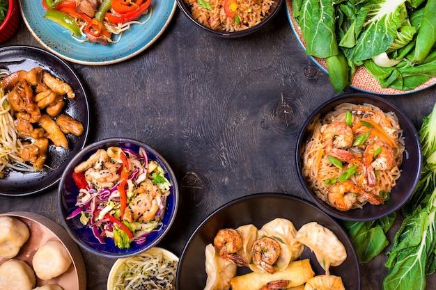 黒の背景に中華料理。麺、米、餃子、鶏肉の炒め物、点心、春巻き