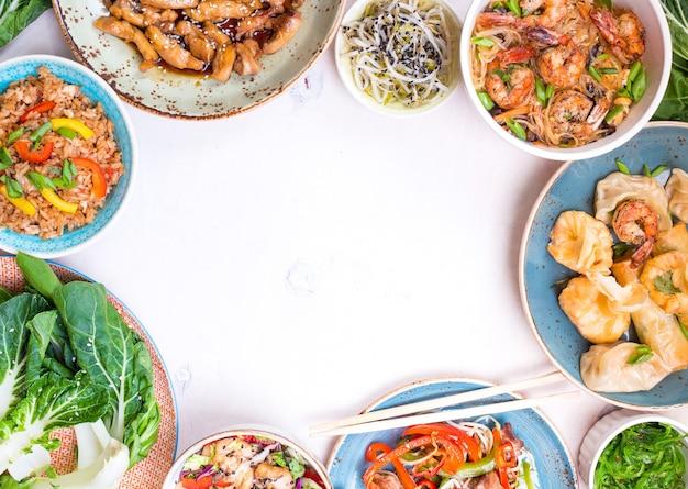 흰색 바탕에 중국 음식입니다. 국수, 볶음밥, 만두, 닭고기 볶음, 딤섬, 춘권