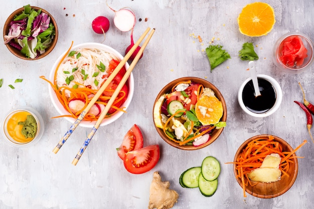 Chinese food salad, noodles with vegetables and nuts on gray stone background