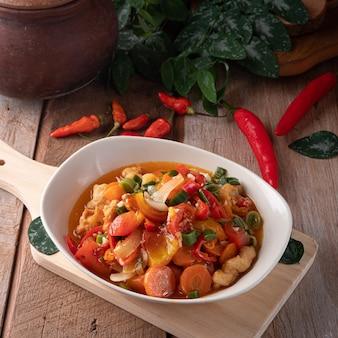 Китайская еда подается на тарелке с чили сбоку