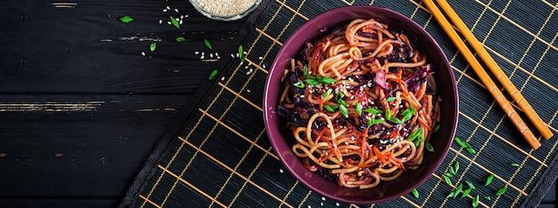 中華料理。赤キャベツと黒の木製の背景にボウルにニンジンのビーガン炒め麺。アジア料理の食事。バナー。上面図