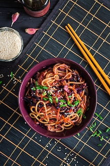 Chinese food. vegan stir fry noodles with red cabbage and carrot in a bowl on a black wooden background.