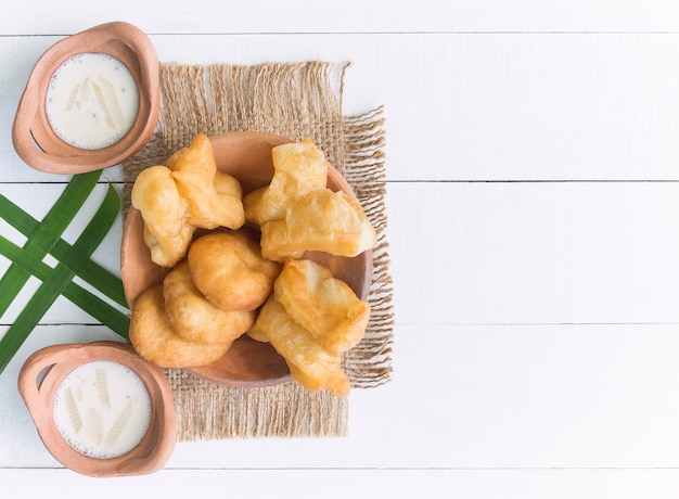 Chinese fried dough or youtiao and soy milk with wooden background for thai breakfast. thai food concept.