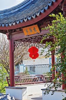 Китайская беседка в саду с китайским красным традиционным фонарем