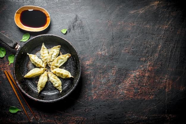 간장을 곁들인 중국 gedza 만두. 어두운 소박한 배경에