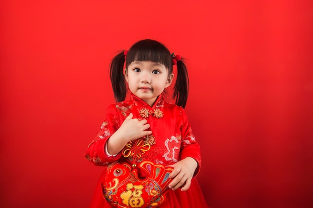 A chinese girl celebrates the spring festival with gold ingots. chinese translation of gold ingots: gold ingot wealth